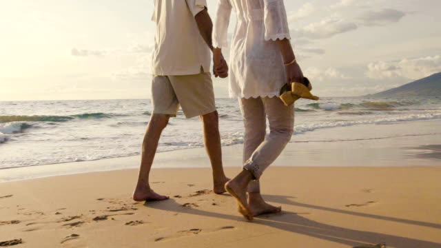 Older Couple Holds Hands and Walks Down the Beach at Sunset Getting Their Feet Wet video
