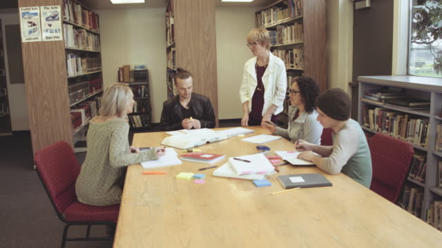 Older female librarian assisting students in a library video