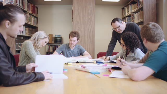 Older male professor assisting a group of students in a library video