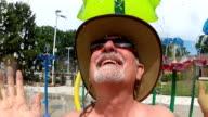 Older man having fun at a water park video