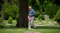 Older man putting US flag in a grave video