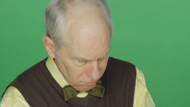 Older man rolls up his sleeves and shows his displeasure, on a green screen studio background video