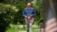 Older man walking through cemetery holding US flag video