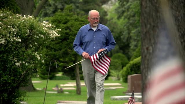 Older man walking through cemetery holding US flag video