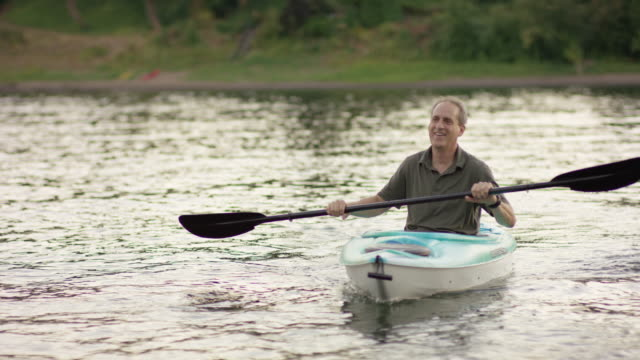 Older mature couple kayaking together during summer video