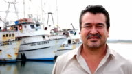 Older Mexican man poses for the camera at fishing docks video