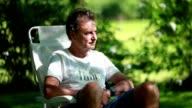 Older retired man in his 60s in outdoor garden enjoying the sunlight video