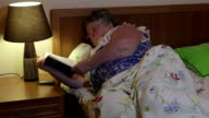 Older woman lying in bed reading book before dozing off at night video