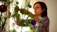 Older woman preparing christmas tree video