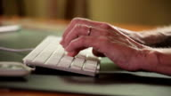 Older woman typing on computer. video