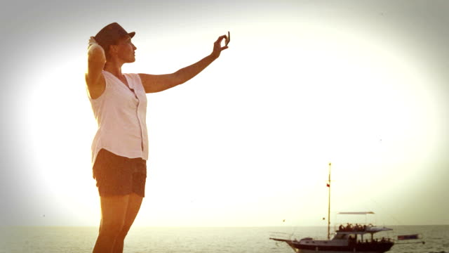 Old-movie effect footage: a woman stands on the seafront and takes a selfie video