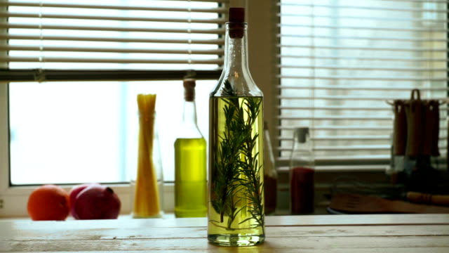 Olive oil bottle on wooden table. Extra virgin olive oil with rosemary herb video