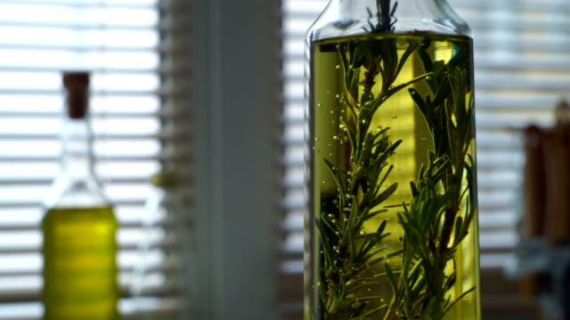Olive oil with rosemary. Rosemary herb falls in olive oil bottle video