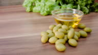Olives lie next to a glass bowl with olive oil video