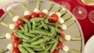 On a large tray canapes from tomatoes, mozzarella and sauce , in the center of the tray pea pods video