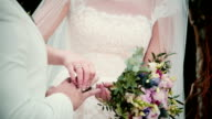 On a wedding day bride puts a golden ring on a groom finger. Close-up exchanging wedding rings video