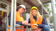 On construction site senior engineer explaining his young blonde trainee some projects video