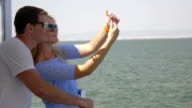 On sea in city of Perea, Greece on a ship young couple doing selfie on a mobile phone video
