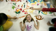 On the floor lies a little girl on top of color pictures, the children paint. video