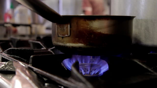 On the gas stove, on a big fire, there is a dirty ladle with a handle video
