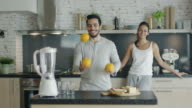On the Kitchen Beautiful Couple Makes Breakfast. Guy Impresses His Lady By Juggling with Oranges. video