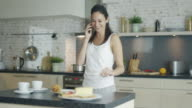 On the Kitchen Beautiful Young Brunette Talks on the Phone and Drinks from the Cup. Also She is Cooking Food. video