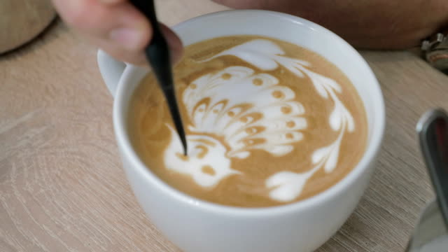 On the table is a cup of coffee with foam and the man draws on the foam pattern video