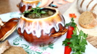 On the table is a pot of soup. The dish is decorated with a sprig of greenery. video