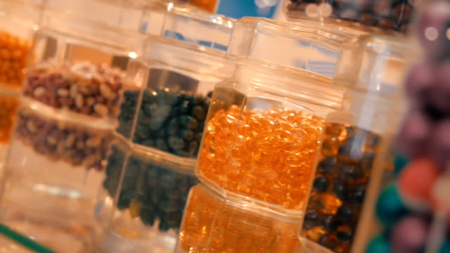 On the transparent surface are glass jars with colorful pills, candy video