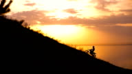 On the way to achieve the goal. motocross bike at sunset on hill climbs video