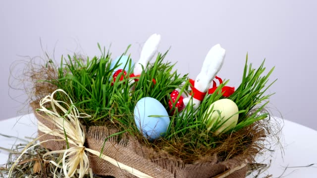 on white background, rotation, The festive Easter composition consists of colored eggs, green young grass and soft figures of white Easter bunnies in red scarves video