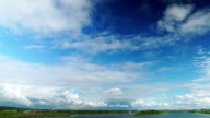 Oncoming white cumulus clouds over landscape video