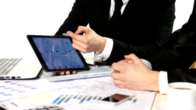 One businessman showing another, developing a business project and analyzing market data information, graphics tablet video