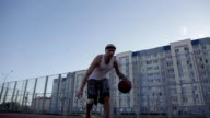 One guy play basketball at district sports ground. video