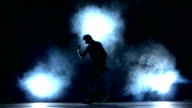 One hip hop break-dancer stylish man in sunglasses dancing, smoke, silhouette video