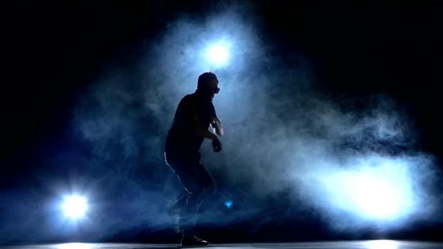 One hip hop break-dancer stylish man in sunglasses starts  dancing, smoke, silhouette, slow motion video