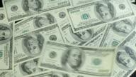One hundred american dollar bills falling through air.Slowmotion video