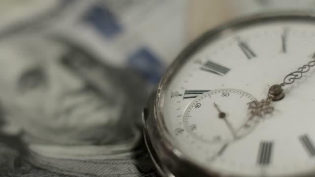 U.S. one hundred dollar bill, pocket watch. Time, money system video