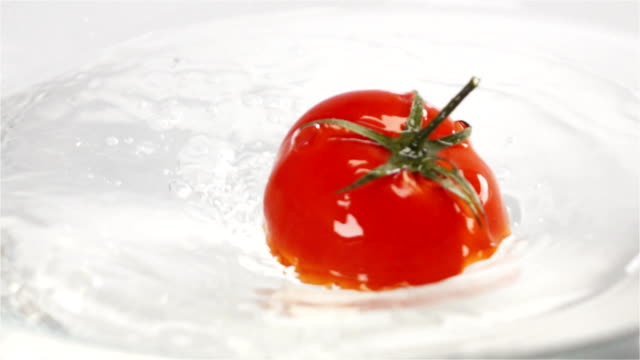 One red ripe tomato with green leaves falls under water video