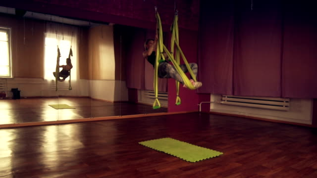 One type of yoga - aerial yoga. A young girl engaged in aerial yoga. This type of yoga on special fabric canvases video