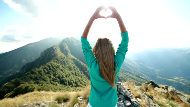 One woman making heart shape at mountain top video