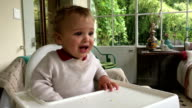 One year old baby crying in high chair. Baby blonde boy crying while waiting for food to arrive video