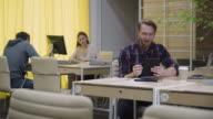 Open space people work, man in headphones speaks with a tablet video