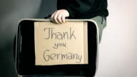open suitcase of refugee with message thank you Germany on cardboard video