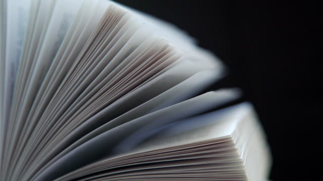Opened book on a dark background isolated : leafing through books video