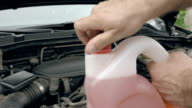 Opening bottle with pink windshield washer fluid video