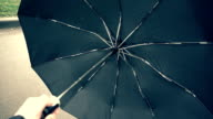 Opening ( closing ) the black automatic umbrella when rain approaching. Slow mo, slo mo video