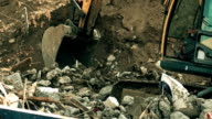Operating excavator and debris. FullHD long shot video