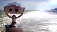 Optical flares footage of a tourist telescope at the seaside with rough waves video