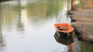 Orange boat floating on canal. video